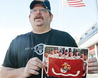 SOMBER REMINDER: Anthony Kolat of New Middletown holds up a picture of fellow Marines with whom he served. He was on one side of a compound in Beirut, Lebanon, on Oct. 23, 1983, when a suicidal truck bomber killed 241 U.S. service members, 220 of whom were Marines.