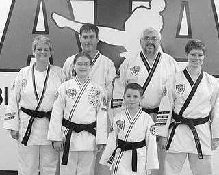 STATE CHAMPIONS: Six students of the Boardman ATA Black Belt Academy won state championships this year in Korean Taekwondo.  Pictured (left to right), first row: Brandon Breznai. Second row: Kim Campos, Caitlin Currier, Brielle Campos. Third row: Shawn Menousak, Robert Long (academy owner). Missing from photo is Yianni Koulianos. All except Long won state titles this year.
