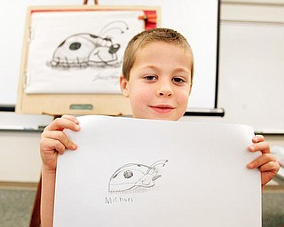 Michael Nittoli, a kindergarten student, shows off his lady bug drawing at Dobbins Elementary School in Poland. The students received an art lesson from Bruce Langton, a children's book illustrator, to promote literacy.