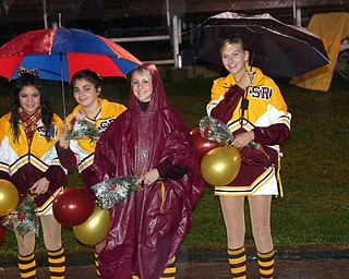 """Waiting in the rain to present Senior cheerleaders flowers are South Range cheerleaders, Kim Miglets, Alex DeRose, Emma Lewis, and Laura McEwan."""