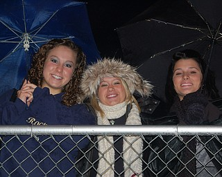 Gia Tkach, Brittany Mazzella and Rachel Collins try to keep dry during the Lowellville-Wellsville game. The rain and mud didn't keep the Rockets from winning 20-8.