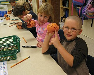 Thereasa Clark and Dean Coman were among the kindergarten students at Ellsworth Elementary School who decorated pumpkins, courtesy of the Green Team.
