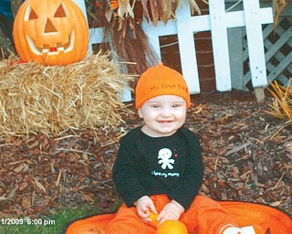 JACK O'LANTERN: Jack Buchner, 9 months, seems pleased with his first jack o'lantern.