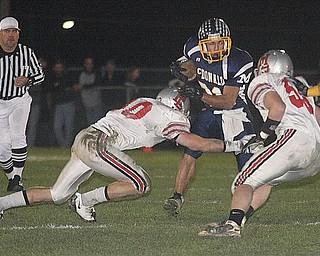 MCDONALD - (31) Zach Tura picks up yardage against (10) Miles Chapman and (36) Jaren Wickham of the Chieftains defense Saturday night. - Special to The Vindicator/Nick Mays