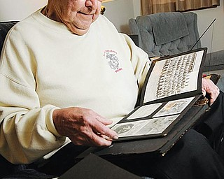 REMEMBERING: Paul Sovik of Youngstown looks through some old pictures that bring back memories of the battles he fought in during World War II in the Pacific. He enlisted in the Marine Corps on Dec. 8, 1941, the day after the Japanese attack on Pearl Harbor.
