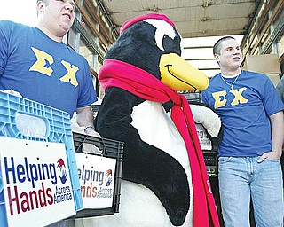 PETE HELPS OUT: Pete the Penguin, Youngstown State University's mascot, was on hand to oversee the loading of food onto a truck on campus as part of the Helping Hands Across America project run by Sodexo Campus Services, YSU's food service vendor. YSU students and Sigma Chi members Steve Tripepi, left, and Josh Lisko did the heavy lifting.