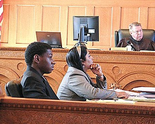 ON TRIAL: Oryan Miller, 20, of Hall Street Northwest, listens to  testimony with his attorney, Sarah Kovoor,  in Trumbull County Common Pleas Court. Miller is on trial in the 2008 death of Cameron  Murray, 21, in Murray's Howland apartment. In the background is Judge Andrew Logan, presiding over the trial.
