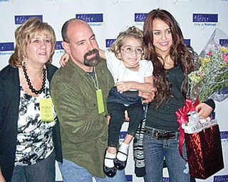 MEETING MILEY: Suzie Mazzocco of Struthers, held by her dad, Tony, gets her picture taken with her favorite singer, Miley Cyrus, before Cyrus' Cleveland concert Sunday. At left is Suzie's mother, Kelley.