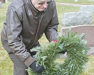 HONORING 28: A group of veterans and members of the Ohio State University Extension Master Gardeners placed wreaths on the graves of 28 veterans Monday in Zion Lutheran Cemetery in Boardman. This is the second year for the ceremony. Shown here is veteran Robert Brienik of Austintown, a member of the Marine Corp League.
