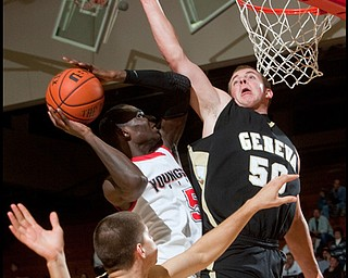 The Vindicator/Geoffrey Hauschild YSU's Sirlester Martin shoots past Geneva defenders Nathan Reep (30) and Matt Blocki (50)during the first half of the game at Beeghley Center on Tuesday evening. 11.24.2009