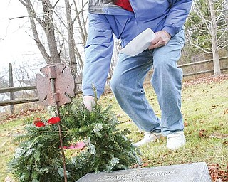 WITH RESPECT: Hugh Earnhart of Poland lays a wreath on a gravestone Monday at Zion Lutheran Cemetery in Boardman. Earnhart helped organize the wreath-laying ceremony last year with the help of the Ohio State University Extension Master Gardeners. Twenty-eight veterans were honored with wreaths that were placed by their graves.