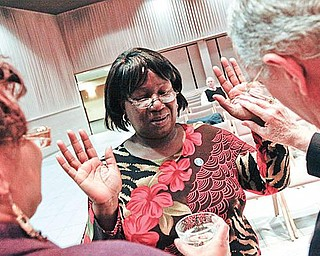 HANDS BLESSED:  Rose Wilkins of Youngstown, center, was one of a dozen people who turned out Monday for the first Blessing of the Hands service,  presented by SouthernCare, a hospice organization.  She had her hands blessed by Dr. Nicholas Mager, right, pastor of the Youngstown First Presbyterian Church, as Sylvia Beard, SouthernCare chaplain, assisted.