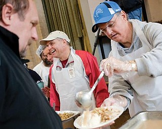 SERVING: State Rep. Ron Gerberry pours gravy over mashed potatoes as Ron Massullo of Poland, regional liaison for Secretary of State Jennifer Brunner, shares a laugh with dinner-goers  at the Salvation Army's annual Thanksgiving feast. They were among 80 to 100 volunteers serving Wednesday's lunch at the Glenwood Avenue facility on the city's South Side.