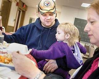 COMMUNITY dinner: Carl Gossett, his daughter, Jessica, 1, and wife, Jody, all of Canfield, enjoy dinner during the Salem Thanksgiving Community Meal at the Memorial Building on Thursday afternoon. The event is in its 17th year.