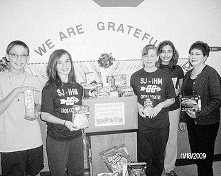 Special to The Vindicator CLASS ACT: The student council at St. Joseph Immaculate Heart of Mary School in Austintown conducted a food drive from Nov. 9 to Nov. 20 as a benefit for the less fortunate in this time of economic hardship. Students took nonperishable items or $1 to a drop-off near the school office. Displaying some of the donations are student council members, are, from left, Wesley Pringle, seventh grade, treasurer; Anny Carroll, eighth grade, president; Maddie Sanders, seventh grade, vice president; AnnaMaria Jadue, eighth grade, secretary; and Sharon Machuga, their adviser, who helped organize the food drive. The donations will be distributed on Tuesday to school families and St. Vincent de Paul.
