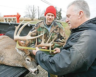 TROPHY BUCK: Kevin Dean, 45, of Alliance, left, watches as Mike Runzo of Beloit, owner of Runzo's Outdoor Sports, measures the antlers of a 16-point buck shot by Dean. Dean, who has hunted for 16 years, said he enjoys the hobby because it is relaxing.