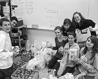 """COLLECTIBLES: Students of St. Patrick School in Hubbard proudly display a portion of the items they have collected during food drives to replenish a food bank operated by St. Vincent de Paul at St. Patrick Church. In addition to food drives, students enjoyed several Friday dress-down days and paid $1 or more to not wear a school uniform. Eighth-grade students collected more than 100 bags of clothing during a """"Poorest of the Poor"""" clothing drive for the needy. The school has donated more than $150 to St. Vincent de Paul and raised more than $200 for the American Cancer Society."""