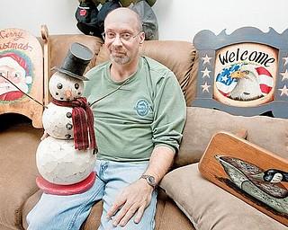 WOOD WORKER: Tom Capp of Cornersburg displays woodworking and painting projects at his apartment. Capp's work will be on display at Piccadilly's Fine Art Galleries in Cleveland's Tremont neighborhood today through next Friday.
