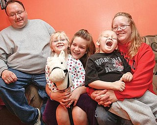 HAPPY FAMILY:  The Howard family, from left to right, includes Mike, Sydney, half-sister Paige DeRhodes, Mikey and Nancy. They're are all smiles on a couch in their Boardman home. Mikey has leukemia and receives treatment at the Akron Children's Hospital Mahoning Valley Beeghly Campus in Boardman.