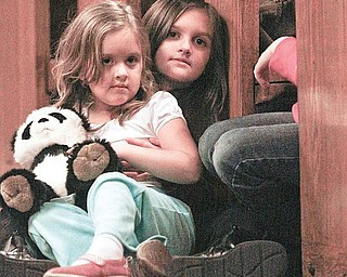 WATCHING: Marissa Orbin, 4, is held by her sister, Angelina, 7, during St. Nick's visit.