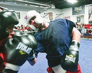 "TAMING THE COBRA:  World middleweight boxing champion Kelly ""The Ghost"" Pavlik lays a right hand into the cringing Ken ""The Cobra"" Sigurani at the South Side Boxing Club. Siguarani, an up-and-coming fighter, went four rounds with Pavlik at an open workout at the club Tuesday."