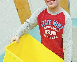 RECYCLE CHALLENGE: Poland North Elementary School fourth-grader Tyler Campbell holds a recycling bin during a program about recycling at his school. The school is participating in a contest to win a trip to Disneyland.