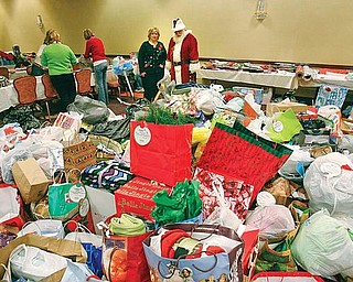 GIVING SEASON: Carol Hitchcock, owner of Home Instead Senior Care, and Santa survey a pile of gifts donated to the Be a Santa for a Senior program. The program will distribute more than 2,500 gifts to about 620 seniors.