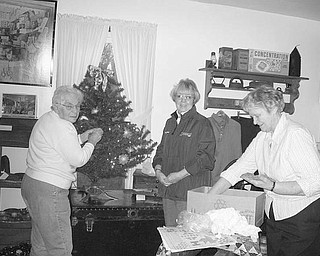 """Special to the Vindicator TREE-TRIMMING: Hubbard Historical Society members, left to right, Joan Gibson, Cecilia Cooper and Lucille Wilson decorate one of the six Christmas trees at the McBride House, 27 Hager St. The house, decorated for Christmas, will be open from 2-5 p.m. Sunday. Gift items for sale include note cards, a historic afghan throw depicting early scenes of Hubbard, the book """"Hubbard"""" by Barbara Emch, a selection of Cat's Meows, and Christmas tree bulbs featuring the Stewart-Kyle Funeral Home and the Tylee Park Gazebo. For information about the open house or any of the gift items, phone Cecilia Cooper at (330) 534-4247."""