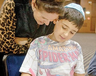 "FAMILY TIME: Jacob Silverman, 10, of Liberty, colors in the fifth Hebrew letter, pronounced ""hey,"" on the side of a dreidel as his mother, Janine Silverman, watches during an event at Temple El Emeth in Liberty on Wednesday."