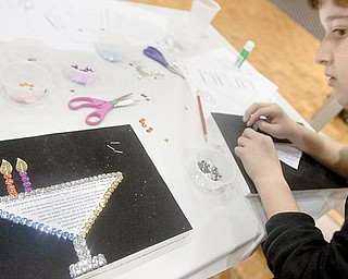Adam Redlich, 11 of Youngstown, takes some tips from a neighbors project while constructing a sequenced menorah during a Hanukkah event with crafts, songs and games at Temple El Emeth in Liberty on Wednesday evening. Blessings said while lighting the menorah candles can be seen in Hebrew script at the center of the menorah.
