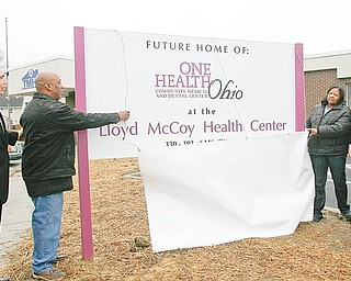 HONORABLE PLACE: Dr. Ronald Dwinnells, far left, chief executive officer of Ono Health Ohio, watches as Lloyd McCoy Sr. and Pam McCoy, at right, unveil the sign for the new medical/dental facility in the Southeast Warren neighborhood. It was announced Monday the facility would be named after the McCoys' son, Lloyd Jr., who was shot and killed earlier this year. At far right is U.S. Rep. Tim Ryan of Niles, D-17th.