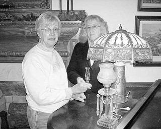 "FIRST NIGHT DISPLAY: Salem Historical Society will participate in Salem First Night activities by creating a display of lamps and lighting fixtures in keeping with the event's ""Light Up Salem"" theme. Janice Lesher, museum curator, at left, shares the story of the courting lamp with volunteer Alice Deatherage as they prepare for the exhibit. Anyone willing to lend unique or interesting lighting fixtures for the display at the Salem Historical Society Museum, 208 S. Broadway Ave, are asked to call (330) 337-8514 Monday or Wednesday mornings. Messages can be left on the answering service. Those enrolling as members of the Historical Society by Jan. 1 will receive a gift packet of Salem Christmas cards or the booklet ""John Brown's Raid."""