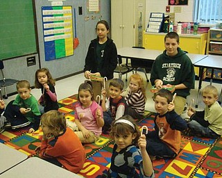 HOLIDAY TREAT: On Dec. 7 two eighth-graders from St. Patrick School in Hubbard visited the kindergarten class at Villa Maria Theresa, 50 Warner Road, Hubbard. They were Rena Ghirardi and Billy Fisher, standing, who read holiday stories and distributed candy treats to the youngsters. They also helped the children decorate a Christmas tree. Pupils in the kindergarten class were surprised to learn their visitors were graduates of Villa Maria.