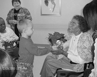 Special to The Vindicator YOUNGSTERS GIVE GIFTS: Youngsters from the Rich Center for Autism at Youngstown State University were accompanied by parents as they delivered 50 poinsettia plants for the holidays to residents of Danridge's Burgundi Manor at 31 Maranatha Drive. The gift giving was part of a Healing Garden Project that began this summer at the center and was financed with a $3,000 grant from the Kennedy Family Foundation. Preston Donatella, a student at the center, is shown as he presented one of the plants, supplied by Chuck's Greenhouse in Salem, to a resident at the manor. In return for the generous gifts, staff members at the manor gave the children a huge stocking filled with toys.