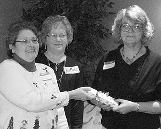 """Special to The Vindicator IT'S OFFICIAL: Niles Chapter of the American Sewing Guild celebrated the Christmas season at a party on Dec. 5 at Ciminero's Banquet Center. Members took time during the festivity to elect officers who will serve during 2010. Named to various positions were Jennie Roberts, president; Lynn Price, first vice president; Barbara Rosier-Tryon second vice president; Diane Wittik, secretary; and Joan Dales, treasurer. A highlight of the event was the presentation of the organization's first """"Member of the Year"""" award. Above, from left, Wittik and Roberts begin their official duties by making the presentation to Rosier-Tryon in recognition of her significant contributions of time and talent to the guild."""