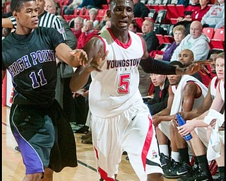 The Vindicator/Geoffrey HauschildYSU's Sirlester Martive (5) loses control of the ball while defended by High Point University's David Singleton (11) during the second half of a game at Beeghley Center on Tuesday evening.