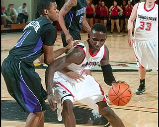 The Vindicator/Geoffrey HauschildYSU's Sirlester Martive (5) makes his way to the hoop while being defended by High Point University's David Singleton (11) during the second half of a game at Beeghley Center on Tuesday evening.