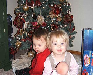 CHRISTMAS PRESENCE: Al and Diane Barnett of Austintown found their granddaughters under their tree. In front, Olyvia Rose Barnett, 18 months, is the daughter of Kevin and Miranda Barnett. Behind her is Savannah Marie Cervone, daughter of Michael and Lisa Cervone.