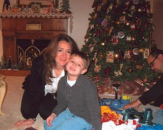 Posing in front of the tree at Beth Hatalsky's home in Mineral Ridge on Christmas morning are her daughter, Tina Miller, and her 6-year-old grandson, Jaxon. Behind them is Beth's son-in-law, Jeff Miller. The Millers are of Poland.