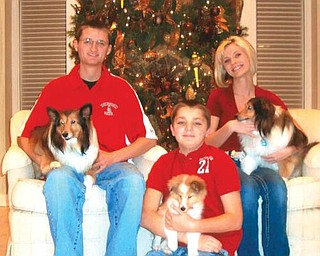 Seated in front of the family Christmas tree, Andrew, Dana and Ross Duffett welcome their new puppy, Frankie, to the family. Joining them are their other dogs, Sophie and Josie.