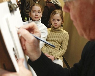The Vindicator/Lisa-Ann Ishihara ---  Sisters Abbey (9) and Alexandra (7) Porter of Girard get drawn by Cartoon & Caricature artist Ed O'Malley of Boardman on the suite level at the Covelli Centre for First Night Youngstown 2010