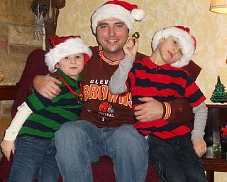 Nicholas and Nathan Burgermyer of Warren are pictured with their uncle, Craig Bash, at the home of another uncle, Jason Burgermyer, in Bazetta on Christmas Eve. They are the great-grandsons of Barb Bradford.