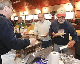 The Vindicator/Lisa-Ann Ishihara -- Gary Robinson of Warren fills the plates of Tim Austin and Art Kantner at Aulizio's Banquet Center in Warren for the free christmas dinner