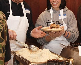 """The Vindicator/Lisa-Ann Ishihara -- Gary Robinson of Warren and Sara Stassinis of Cortland fills the plates attendants at Aulizio's Banquet Center in Warren for the free christmas dinner. Sara said she """"wants everyone to know that this holiday we should remember in our hearts that Jesus is our lord and savior and its a blessing to help all of these beautiful people. """""""