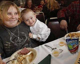 The Vindicator/Lisa-Ann Ishihara -- Tiffany Cline (12) and Bobby Cline (2) of Warren enjoy the holiday feast at Aulizio's Banquet Center in Warren for the free christmas dinner***Tiffany is not Bobby's sister.. I believe she is his aunt**