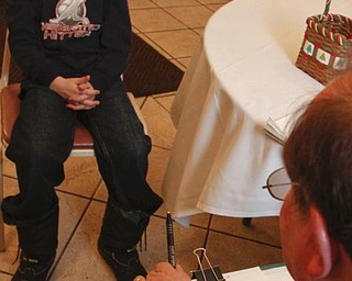 The Vindicator/Lisa-Ann Ishihara -- Travis Wagner-Lewis (10) of Niles gets drawn by Rick Muccio of Warren at Aulizio's Banquet Center in Warren during the free christmas dinner