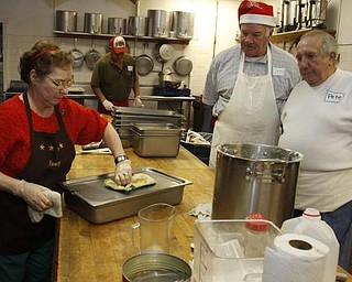 The Vindicator/Lisa-Ann Ishihara -- Nancy Jenkins of Warren,John Messersmith of Hartford and Pete Orfanos of Warren volunteer their time in the kitchen at Aulizio's Banquet Center in Warren for the free christmas dinner