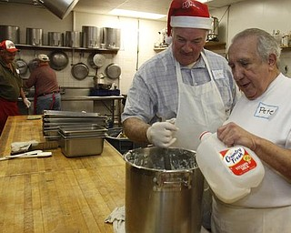The Vindicator/Lisa-Ann Ishihara -- John Messersmith of Hartford and Pete Orfanos of Warren volunteer their time in the kitchen at Aulizio's Banquet Center in Warren for the free christmas dinner