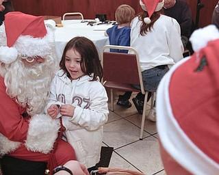 The Vindicator/Lisa-Ann Ishihara -- Destiny Goetz (4) of Warren talks with Santa at Aulizio's Banquet Center in Warren during the free christmas dinner