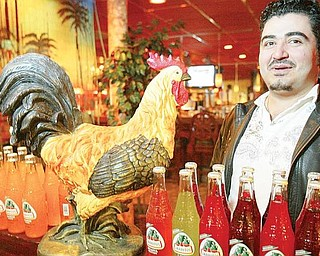 PROUD OWNER: Israel Zambrano stands near a rooster in his Boardman restaurant, Los Gallos. He named the restaurant after his nickname, which means rooster in English.